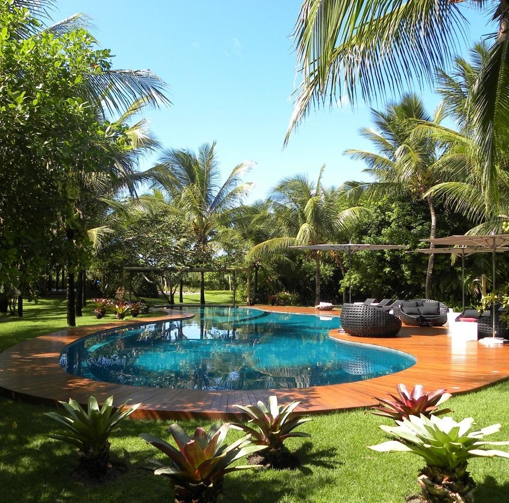 Junto ao deck da piscina com formato orgânico, o paisagista Marcelo Faisal dispôs coqueiros (Cocos nucifera L.) e bromélias. Para o relaxamento dos usuários, confortáveis móveis de fibra e ombrelones. O jardim com 11 mil m², de uma residência em Trancoso, na Bahia, é baseado em plantas regionais, características da restinga