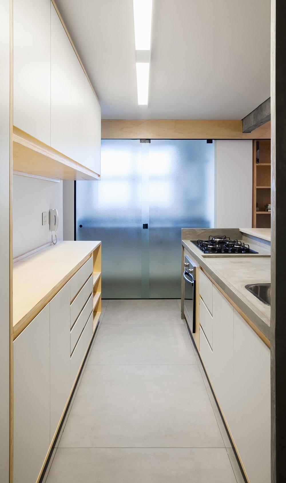 Na cozinha do apartamento reformado pelo Grupo Garoa Arquitetos, a bancada que recebe a pia e o cooktop (à dir.) foi armada e moldada em concreto. Os móveis feitos em marcenaria têm acabamentos neutros e no piso, um porcelanato que se assemelha ao cimento queimado. Ao fundo, a área de lavanderia é fechada por porta de correr em vidro