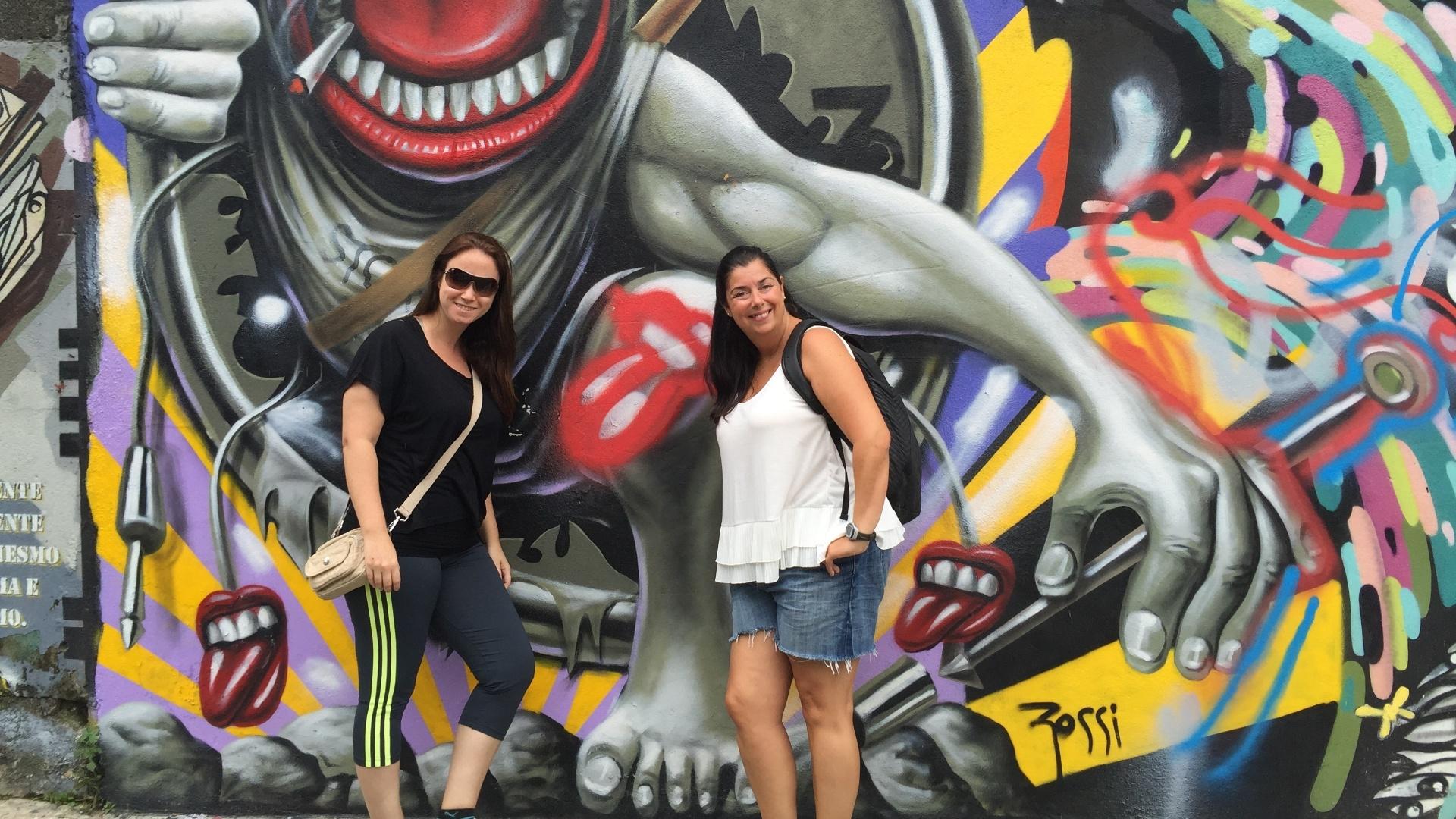 27.fev.2016 - As amigas de Buenos Aires Sabrina Muñoz e Lucila Hahloh foram até ao Beco do Batman para tirar foto com o grafite feito por Ron Wood