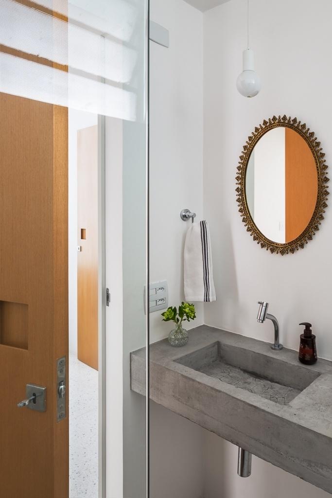 O banheiro social do apê 62, em São Paulo, se transformou em um lavabo, graças a reforma planejada pelo escritório Vitrô Arquitetura. O espaço foi equipado com uma bancada de concreto com pia embutida. O clima industrial é suavizado, porém, com o uso do espelho com moldura delicada