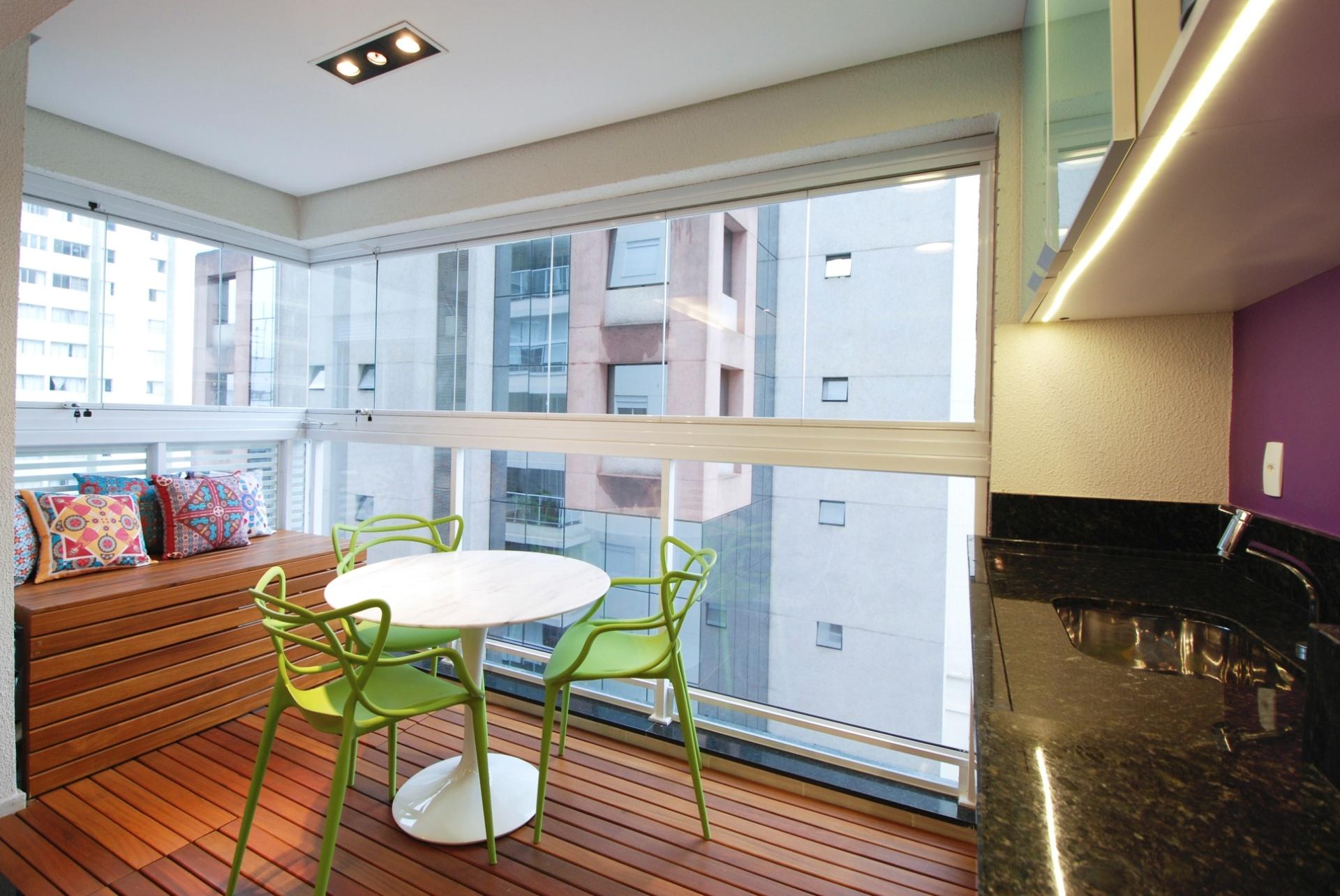 Para evitar quebra-quebra, Leandro Matsuda instalou sobre o piso cerâmico original da varanda um deck de madeira. O mesmo material esconde o ar-condicionado e estrutura um banco (à esq.). Como a varanda está integrada aos ambientes internos, o arquiteto optou pelo fechamento em vidro, alinhado ao guarda-corpo. No espaço, as três cadeiras verdes do modelo Allegra (Sun House) são feitas de polipropileno e foram combinadas à mesa com design do finlandês Eero Saarinen