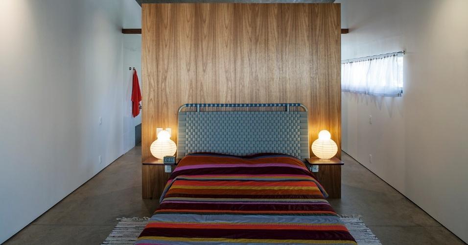 Dentro da suíte, chama atenção o sobe e desce do forro, que ajuda a criar uma percepção visual ampliada do espaço reduzido. A janela fita (à dir.) é protegida por grades. A cabeceira está encostada em uma parede solteira revestida de madeira (freijó) e o piso é de concreto polido. A Slice House, em Porto Alegre (RS), tem projeto do escritório Procter-Rihl