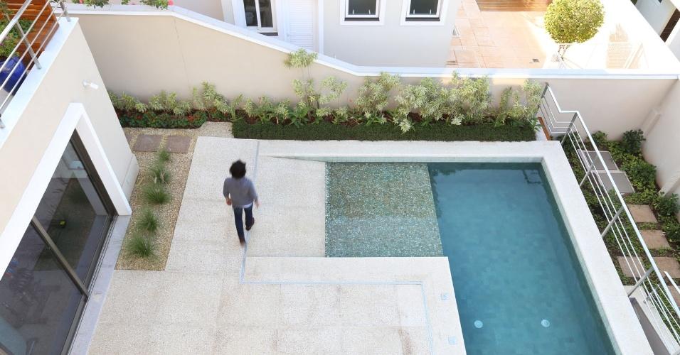 A piscina da casa Campinas é revestida com pedras vulcânicas (Palimanan) e a prainha tem seixos rolados isolantes. O piso mais claro, ao redor do tanque, é feito em peças da Castelatto, compostos de material cimentício com cacos de conchas recicladas. A arquitetura é assinada por Teresa d'Ávila