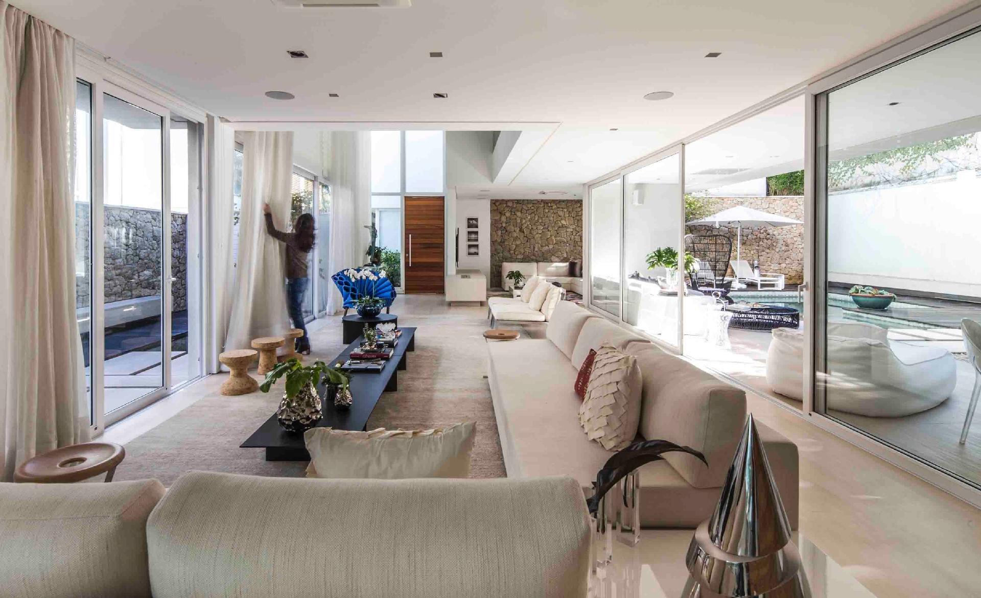 A luz natural inunda os interiores da casa graças às portas corrediças envidraçadas nas laterais da sala de estar, que também promovem a ventilação cruzada. De um lado do living está a piscina com spa, do outro, os jardins. O condomínio Bauhaus é um projeto da arquiteta Monica Drucker