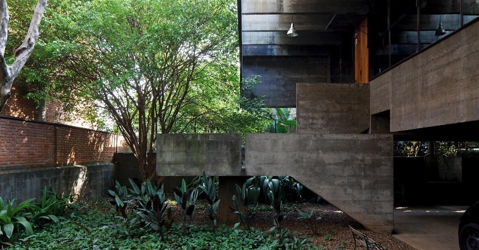 O térreo da casa Butantã, projetada por Paulo Mendes da Rocha, é uma praça que combina concreto e jardim, onde se situa a escada que dá acesso ao pavimento superior e principal. Destaque para o beiral, com pergolado em balanço de três metros
