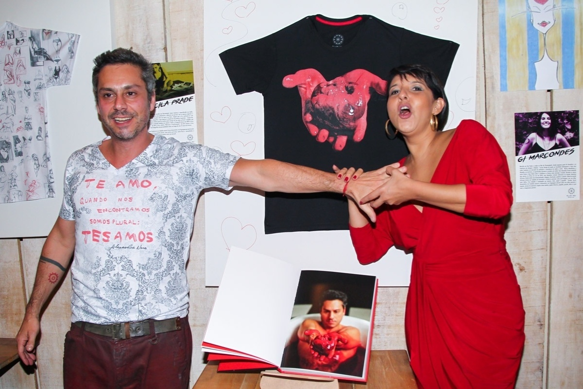 17.out.2015 - Alexandre Nero compareceu ao lançamento da marca de camisetas da irmã, Andrea Nero, em São Paulo. Durante o evento, o ator brincou com a fotógrafa Priscila Prade e tentou apalpar o seio dela, mas foi contido pela convidada.