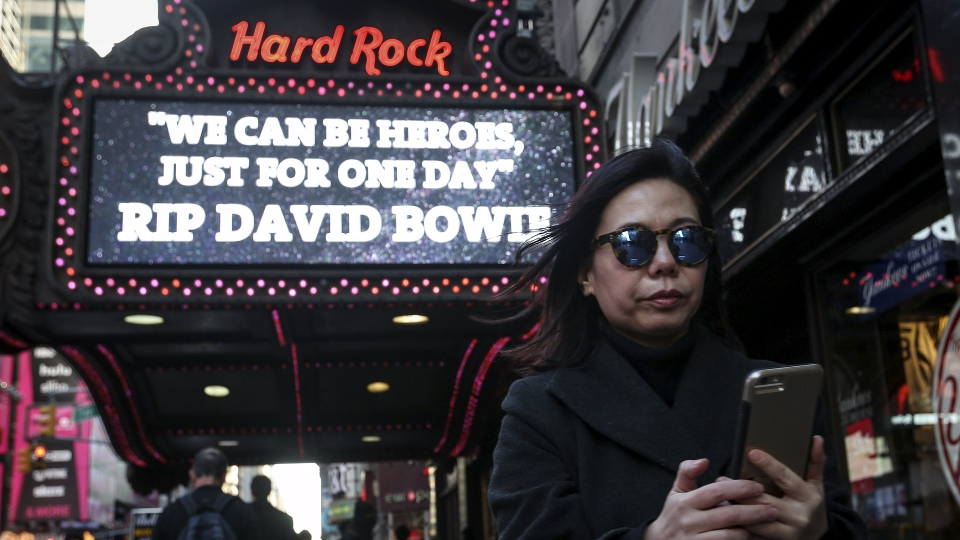11.jan.2016 - Fã de David Bowie tira foto do letreiro do Hard Rock Café, na Times Square, em Nova York, nos Estados Unidos