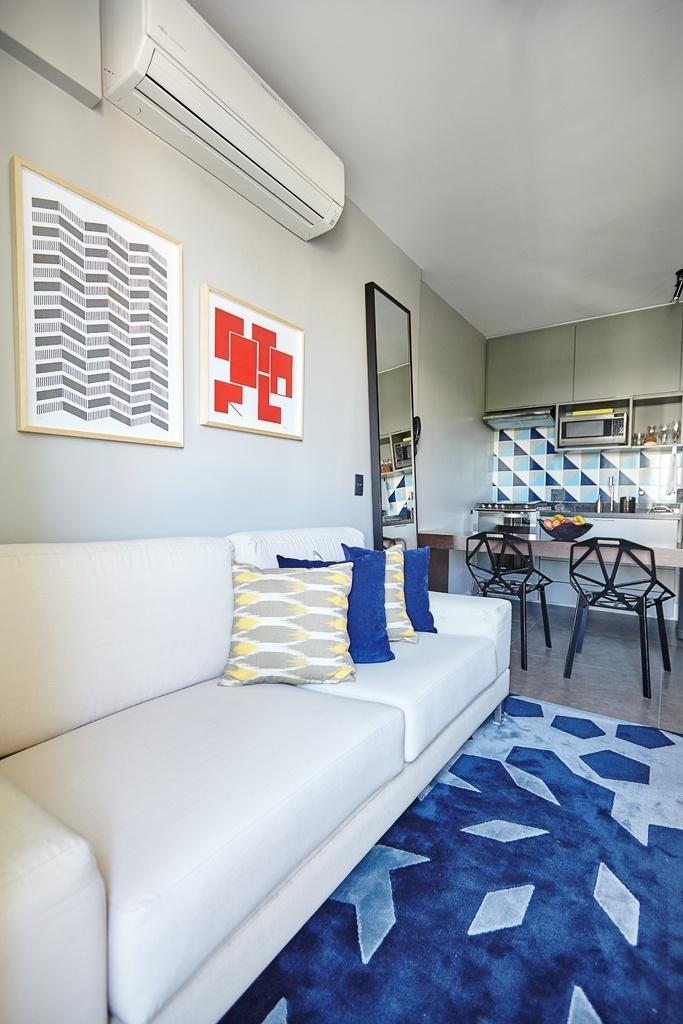 Na área do estar, as gravuras na parede sobre o sofá são do artista Rubem Pondé. Os quadros completam a decoração com toques de cor no tapete (Oppa) e nas almofadas. Os tons de azul e as pitadas de amarelo combinam com a parede da cozinha (ao fundo), revestida com azulejo Kit Triangulo, da Lurca. O apê com 29 m² fica em São Paulo e tem interiores assinados pelo escritório Notar Design