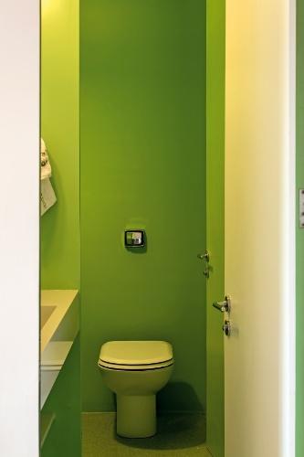 A arquitetura de interiores desenvolvida pelo escritório Pascali Semerdjian para a reforma do Apartamento FT, em São Paulo, distribuiu cores marcantes nas áreas molhadas, como cozinha, lavabo e banheiro. Na foto, o lavabo com paredes verdes serve à sala da jantar
