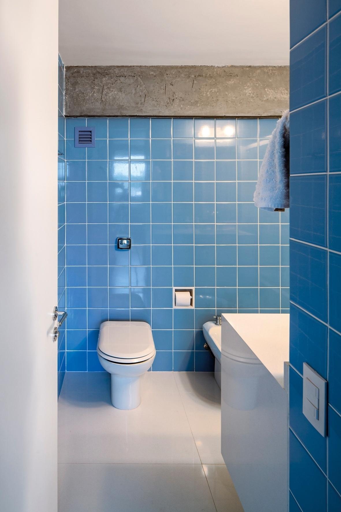 Até no banheiro do Apartamento FT as vigas estruturais de concreto foram descascadas. Aparentes, elas combinam com novos azulejos azuis (15 cm x 15 cm), que remetem à estética original do edifício em São Paulo, construído nos anos 50. A proprietária não quis ter uma suíte e deixou o banheiro separado do dormitório, aberto para uso da área social integrada, com escritório e salas de estar e TV