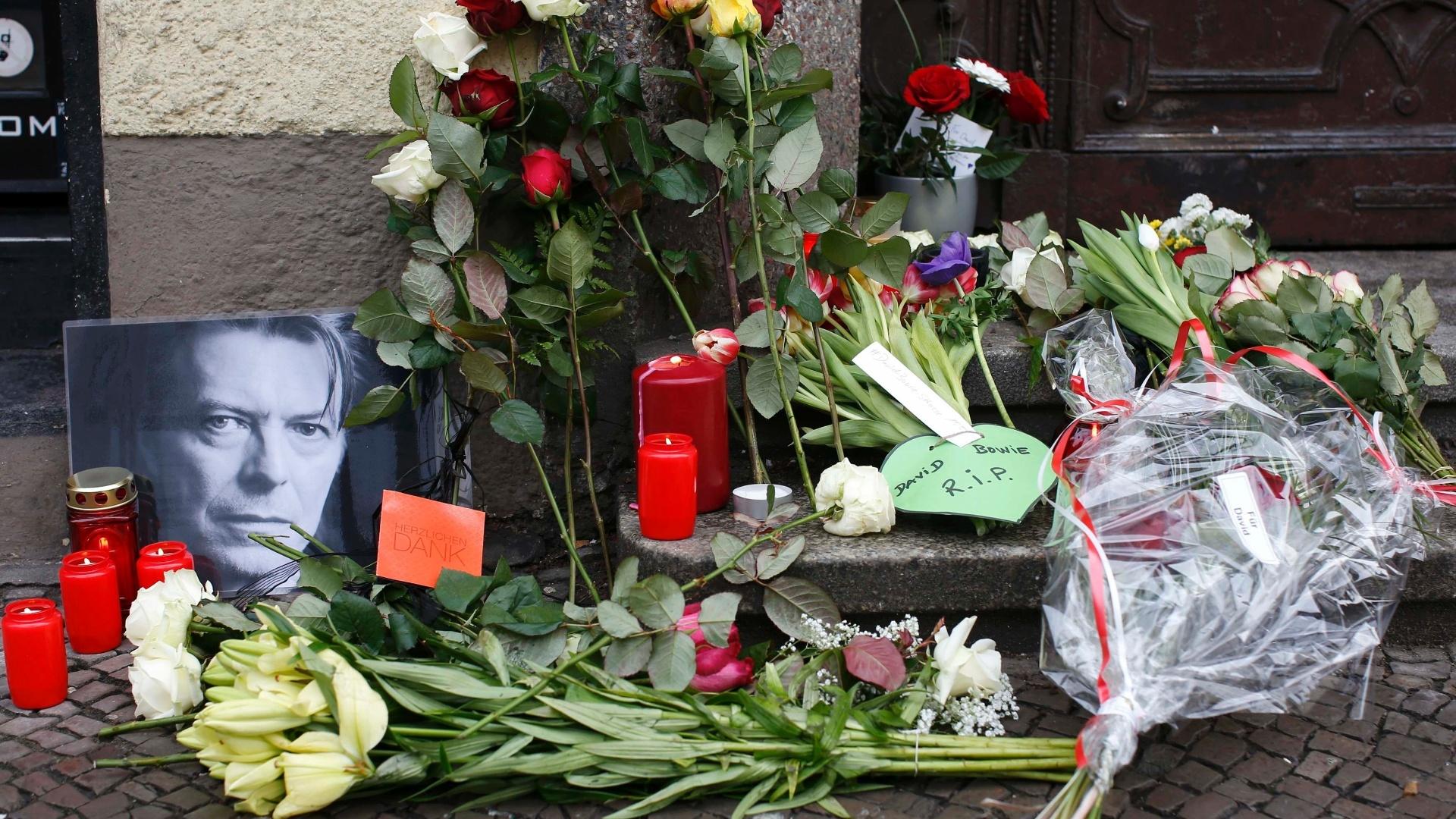 11.jan.2016 - Flores e velas são acesas ao lado de um retrato de David Bowie deixado por fãs em frente ao apartamento onde o cantor morava, em Schoeneberg, em Berlim, na Alemanha