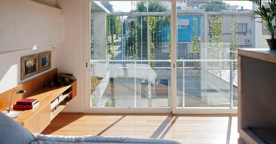 O dormitório principal, assim como outros ambientes do pavimento íntimo, tem piso em assoalho de madeira e portas de correr envidraçadas, que oferecem vista direta para o pátio verde interno. A casa Ibiray é um projeto dos arquitetos Lucho Oreggioni e Sonia Prieto