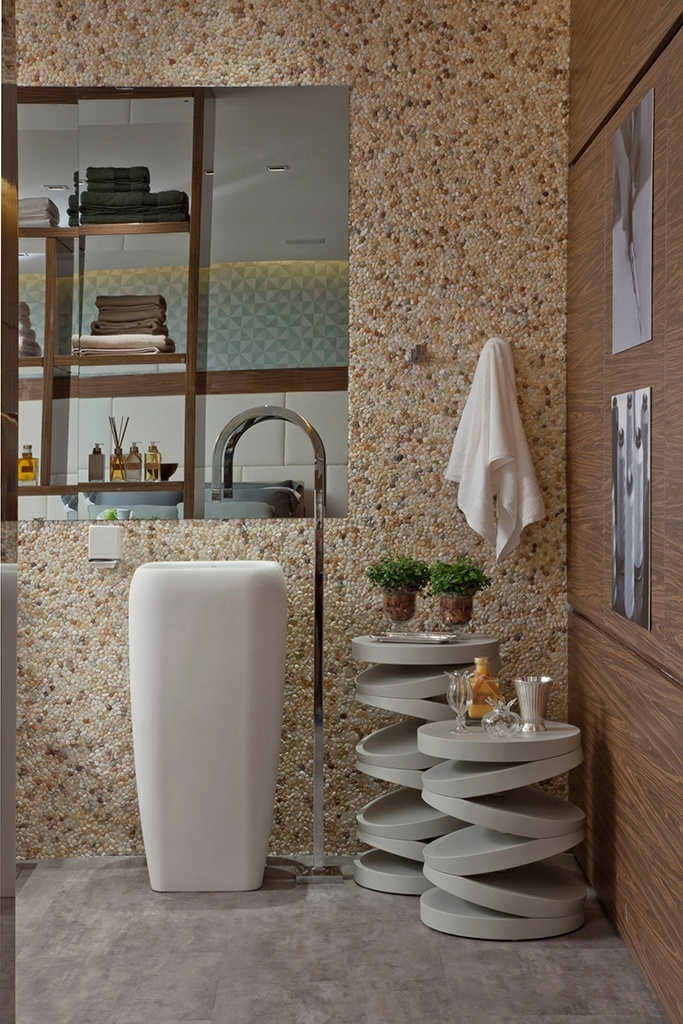 Rústico chique - O revestimento da parede com mini seixos (Colormix) dá o tom desta sala de banho projetada pela designer de interiores Patrícia Pasquini. Ajudam a compor o ambiente, um grande espelho, que esconde a TV-LCD, a banheira oval feita de resina (Banho Mais), a cuba Deca e as mesas laterais da Florense