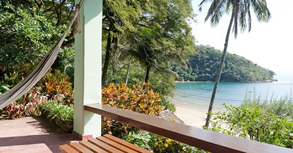 A varanda, com vista para o mar, no sítio da Ilha Grande (RJ), tem rede, banco de madeira e detalhes em cróton (Codiaeum variegatum), planta arbustiva de folhagem muito exuberante. Projeto de paisagismo é da arquiteta Tania Manela Kurc