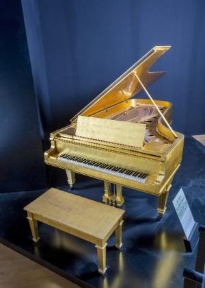 Piano de cauda folheado a ouro de Elvis Presley, que ficava na sala de música de Graceland, em Mênfis, no Tennessee
