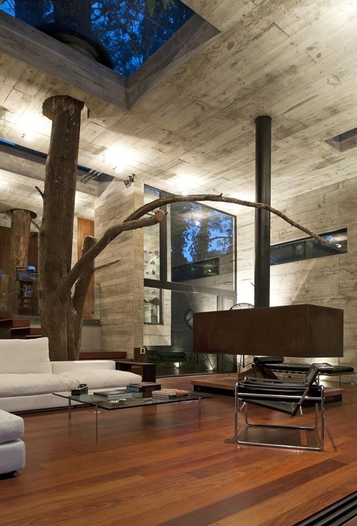 A Casa Corallo, idealizada pelo escritório Paz Arquitectura, está localizada em um bosque montanhoso na Cidade da Guatemala, no país homônimo, e incorpora uma árvore. A distribuição dos espaços foi feita de forma a respeitar o exemplar, para que ele crescesse livremente. Veja que a estrutura de concreto  da sala foi pensada para acoplar o tronco como se fosse um dos pilares (mas sem a função de sustentação)