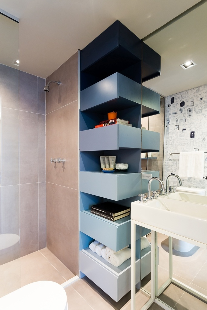 A marcenaria do banheiro de hóspedes é laqueada e conta com nichos na vertical, decorados com degradê de tons de azul. O apê Alvorada tem projeto de interiores assinado pelo escritório Suite Arquitetos