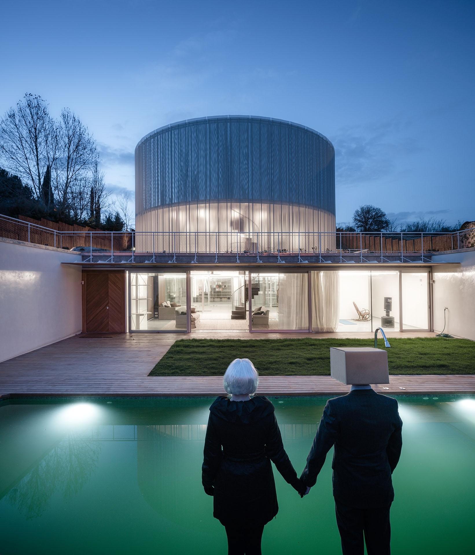 No subsolo da casa Tobogan está a piscina com deck de madeira e gramado. Ao fundo podemos ver o 'living' envidraçado. O projeto é do escritório Z4Z4 Architects e fica em Madri, Espanha