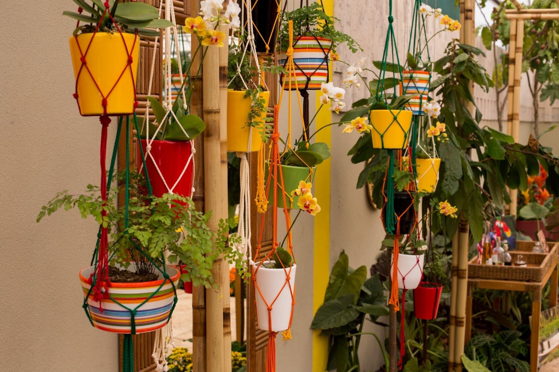 Tem apenas um cantinho livre em casa pra montar seu jardim? Inspire-se na proposta da engenheira agrônoma e paisagista Cintia Rua para o Espaço Beleza Natural: pendure vasos de orquídeas e helicônias em um pequeno pergolado de bambu com o auxílio de cordas coloridas. Fica lindo! | O ambiente pode ser visto na mostra de paisagismo da Expoflora até 27 de setembro de 2015 em Holambra (SP)