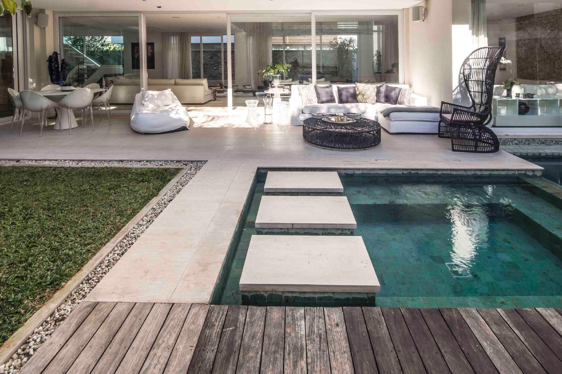 O deck de madeira de demolição contorna a piscina e o spa e contrasta com o piso de mármore da varanda. Ali, o mobiliário é confortável com pufes e sofás para o descanso. A casa no condomínio Bauhaus foi projetada pela arquiteta Monica Drucker