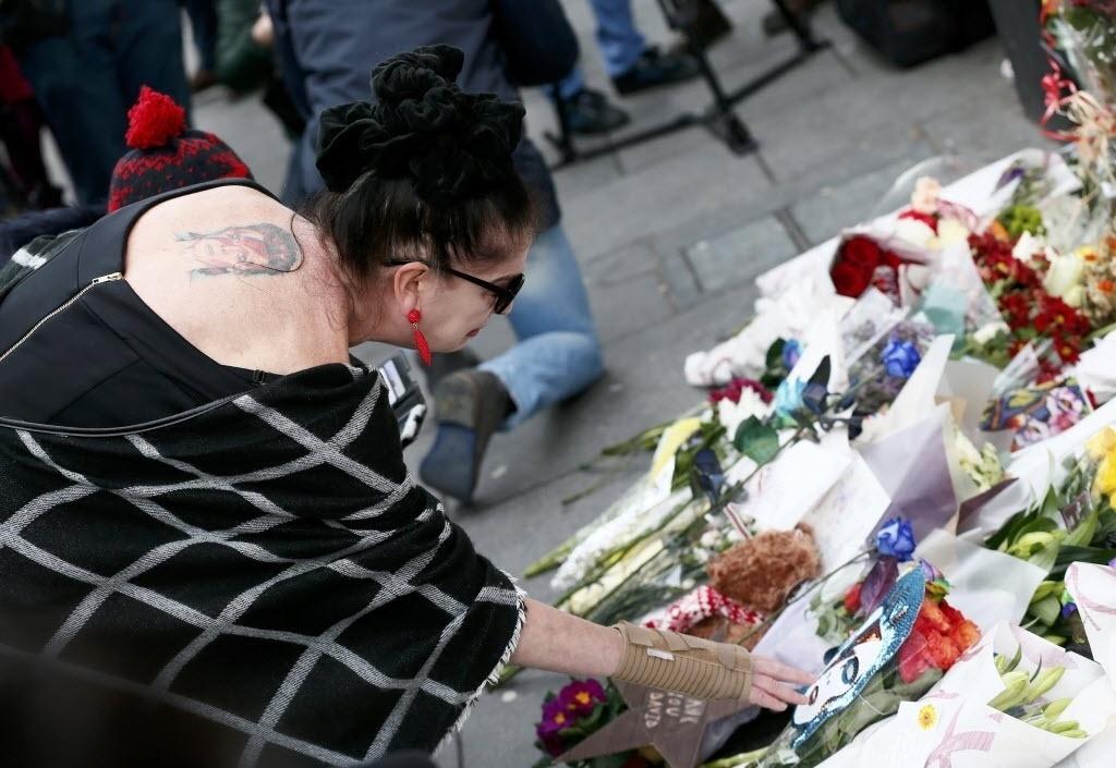 11.jan.2015 - Mulher com tatuagem de Ziggy Stardust visita memorial em homenagem a David Bowie em Brixton, Londres