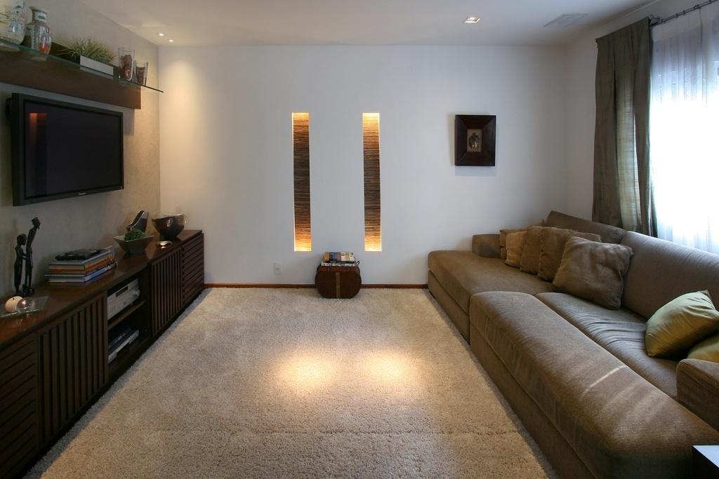 Com 15,5 m², este projeto de Karina Korn propicia conforto aos usuários: a parede, que foi revestida com papel, acomoda a TV LED 42