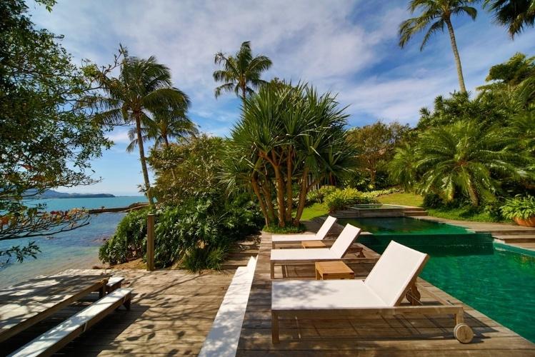 jardim deck de madeira:-area-de-piscina-voltada-para-a-praia-e-recoberta-por-deck-de-madeira