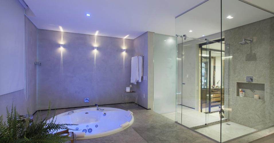 O banheiro da suíte máster fica um nível acima do quarto e tem acabamento em limestone. Com iluminação que proporciona relaxamento, a área de banho é composta por uma banheira e um box envidraçado. Sidney Quintela do SQ+ Arquitetos Associados assina a casa em Salvador (BA)