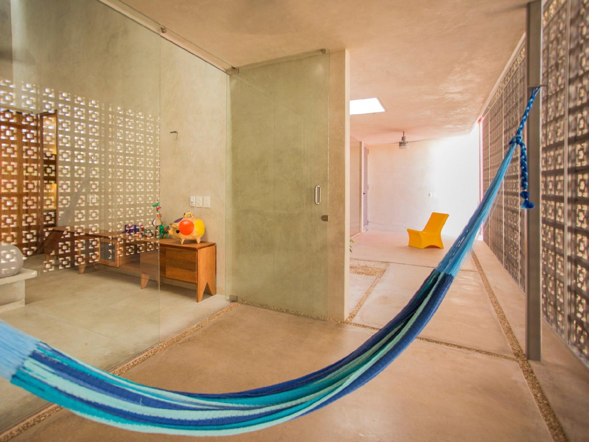 A varanda atende o dormitório e se estende até a área de convivência, que integra cozinha e salas de estar e jantar. Este pátio interno é separado do terraço por uma parede de cobogós. Ao fundo, uma cadeira amarela (DEC Design) foi escolhida pelo escritório Taco - Taller de Arquitectura Contextual, que assina os interiores e a arquitetura da casa Gabriela, no México