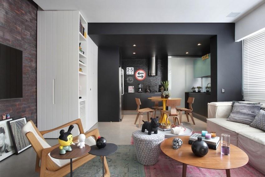 O projeto desenvolvido pelo Studio ro+ca, em Ipanema, no Rio, tem uma cozinha com base preta integrada ao living. A decoração do espaço é leve e descontraída, pois incorpora pontos de cor e texturas à sobriedade do negro