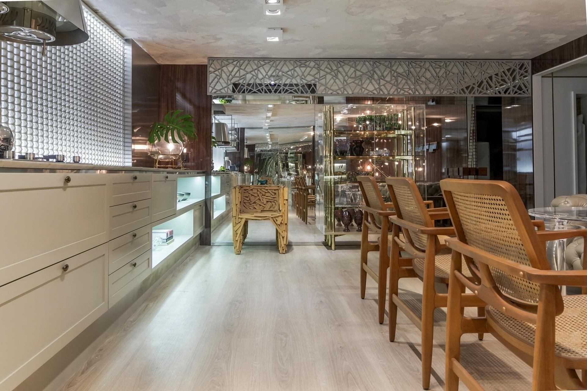 Casa Cor Paraíba 2016 - Para a Cozinha da Chef, Raquel Claudino e Geórgia Suassuna desenharam um painel vazado de aço, que emoldura o topo da parede espelhada. À esquerda, na janela, a cortina Parametre (HunterDouglas) é um painel de ecorresina recortado, que pode ser usado como divisória. Os elementos são contemporâneos e combinam com o mix de acabamentos e estilos de móveis do espaço