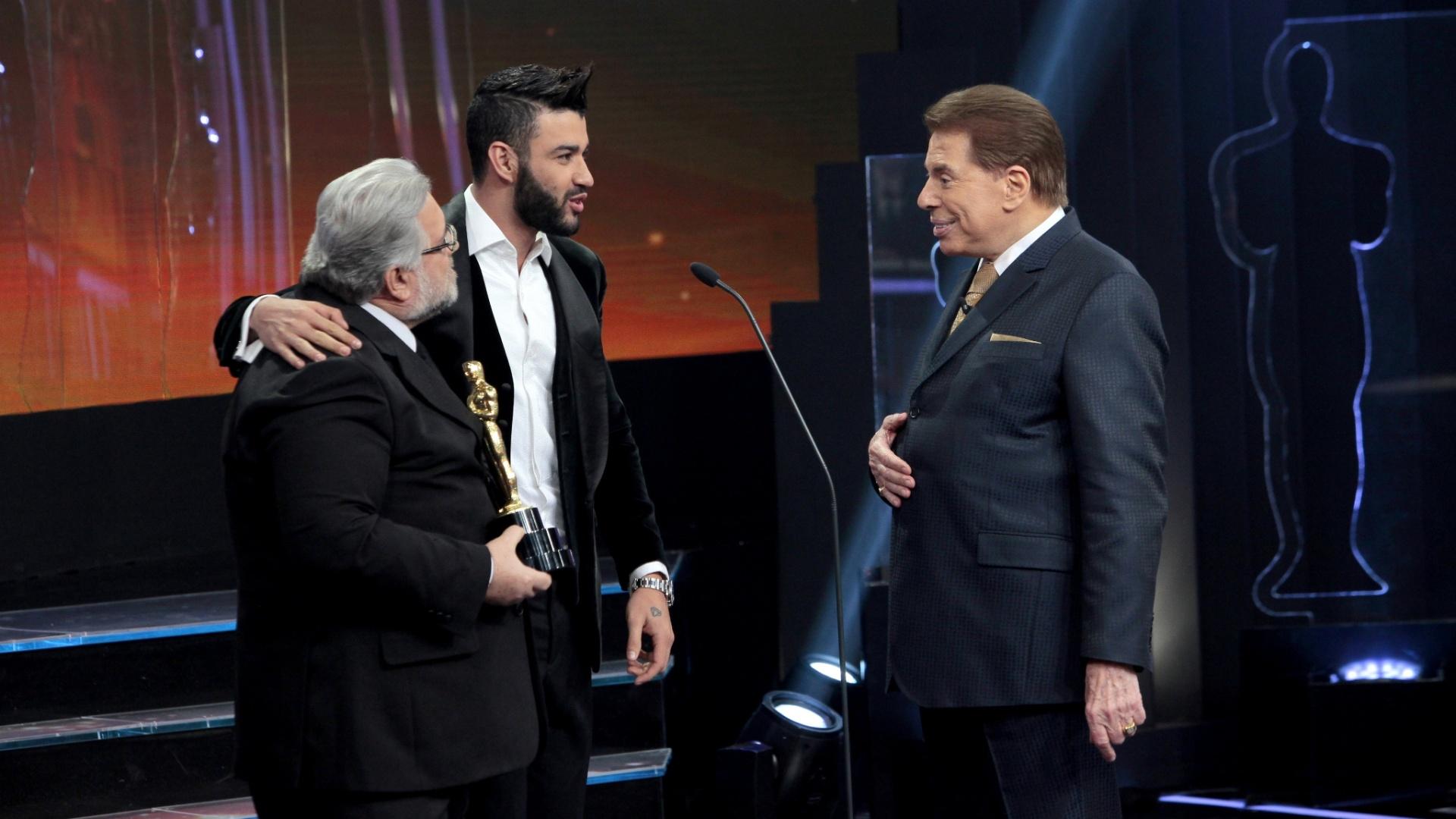 Silvio Santos e o jurado Leão Lobo recebem o cantor Gusttavo Lima no palco do Troféu Imprensa