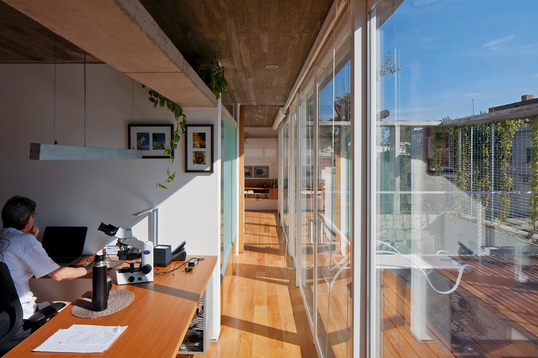 O escritório se liga ao dormitório principal (ao fundo) por um corredor junto às portas e fechamentos de vidro na casa Ibiray. A disposição dos cômodos aproveita amplamente a luz natural e faz a arquitetura de Lucho Oreggioni e Sonia Prieto mais fluida e leve