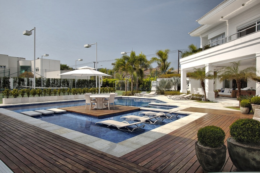 Na casa Acapulco é possível ficar dentro da piscina, sob a sombra e sem se molhar: há uma espécie de ilha (deck de madeira) que dá sustentação à mesa e ao ombrelone. As espreguiçadeiras estão posicionadas na áreas mais rasa do tanque, a prainha. O projeto de decoração é assinado por Bianka Mugnatto