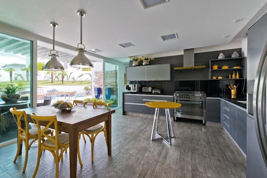 Grandes portas corrediças de vidro separam a cozinha da área externa, coberta pelo pergolado de concreto, sob o qual está uma mesa para refeições. O espaço se volta para piscina da casa Alphaville, desenhada pela arquiteta Carla Kiss