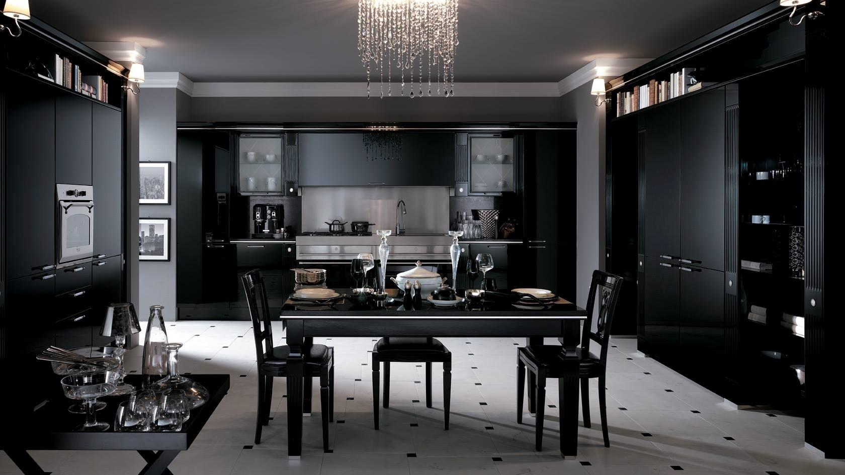 O preto também combina com o clássico, como neste exemplo em que a marcenaria é rebuscada. O matiz foi aplicado nas paredes, armários e principais móveis, mas há