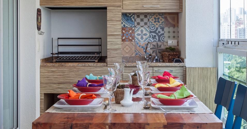 Na varanda gourmet com 18 m², Cristiane Schiavoni planejou a marcenaria que abriga a churrasqueira, uma pia e armários para acomodar acessórios e eletrodomésticos. Para compor um espaço descontraído, a mesa para refeições combina cadeiras azuis e um banco de madeira
