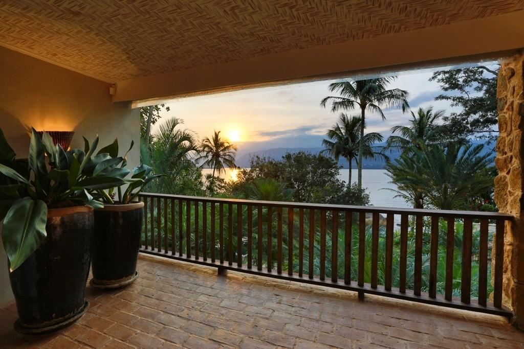 Da varanda da casa em Ihabela (SP) é possível apreciar o pôr-do-sol sobre o mar, além do exuberante jardim criado pelo paisagista Alex Hanazaki com palmeiras, coqueiros, pândanos e helicônias, entre outras espécies tropicais