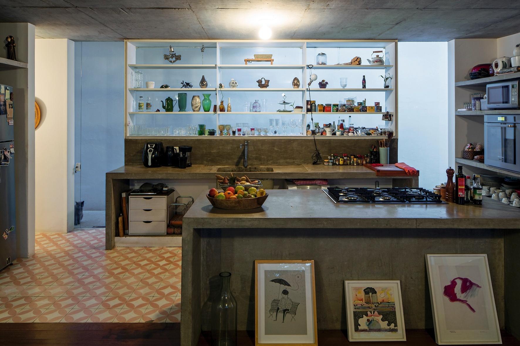 A cozinha da casa LP, projetada pelo escritório Metro Arquitetos, conta com bancada, prateleiras e ilha de cocção em concreto. Integrado com o living, o ambiente tem piso de ladrilhos hidráulicos e uma estante metálica disposta à frente do fechamento de vidro, que funciona como janela