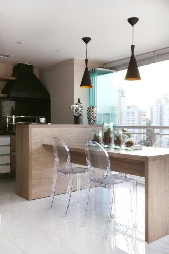No projeto do Amadeu + Castro Arquitetura, a varanda gourmet tem uma churrasqueira e uma bancada acoplada a uma pequena mesa de jantar, com quatro lugares. Sobre o móvel, os vasos de vidro com suculentas combinam com as cadeiras em acrílico