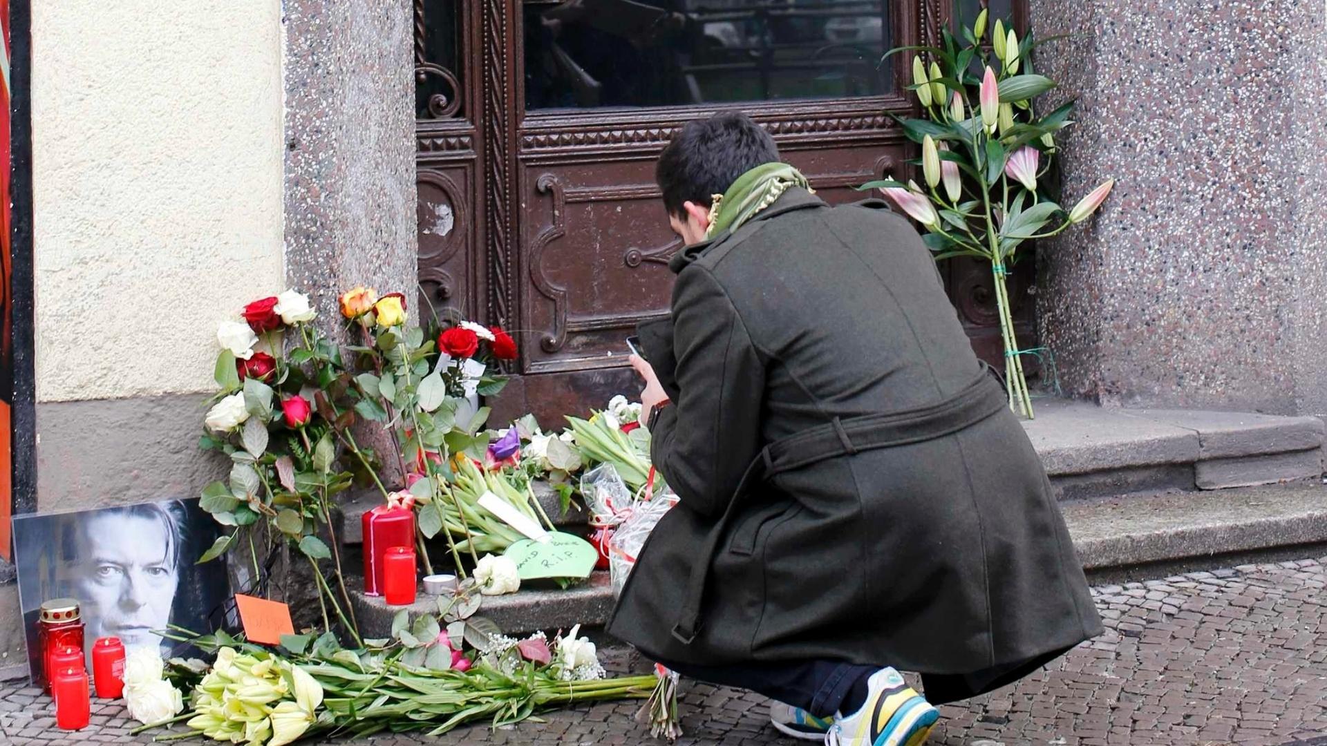 11.jan.2016 - Fã tira fotos das flores deixadas em frente ao apartamento onde David Bowie estava morando em Berlim, na Alemanha.