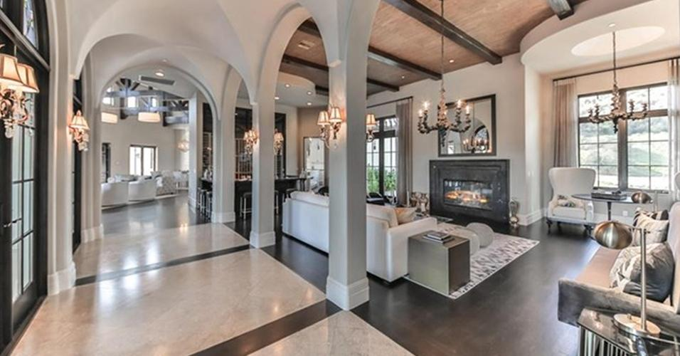 Uma das salas de estar da mansão que Britney Spears colocou à venda por US$ 8,9 milhões (o equivalente a R$ 32 milhões, segundo cotação do dia 13.maio.2016) conta com janelões, lustres e arandelas, que deixam o espaço bem iluminado. A cartela de cores contrasta a base escura e os móveis claros e é pontuada por tons de cinza prateado