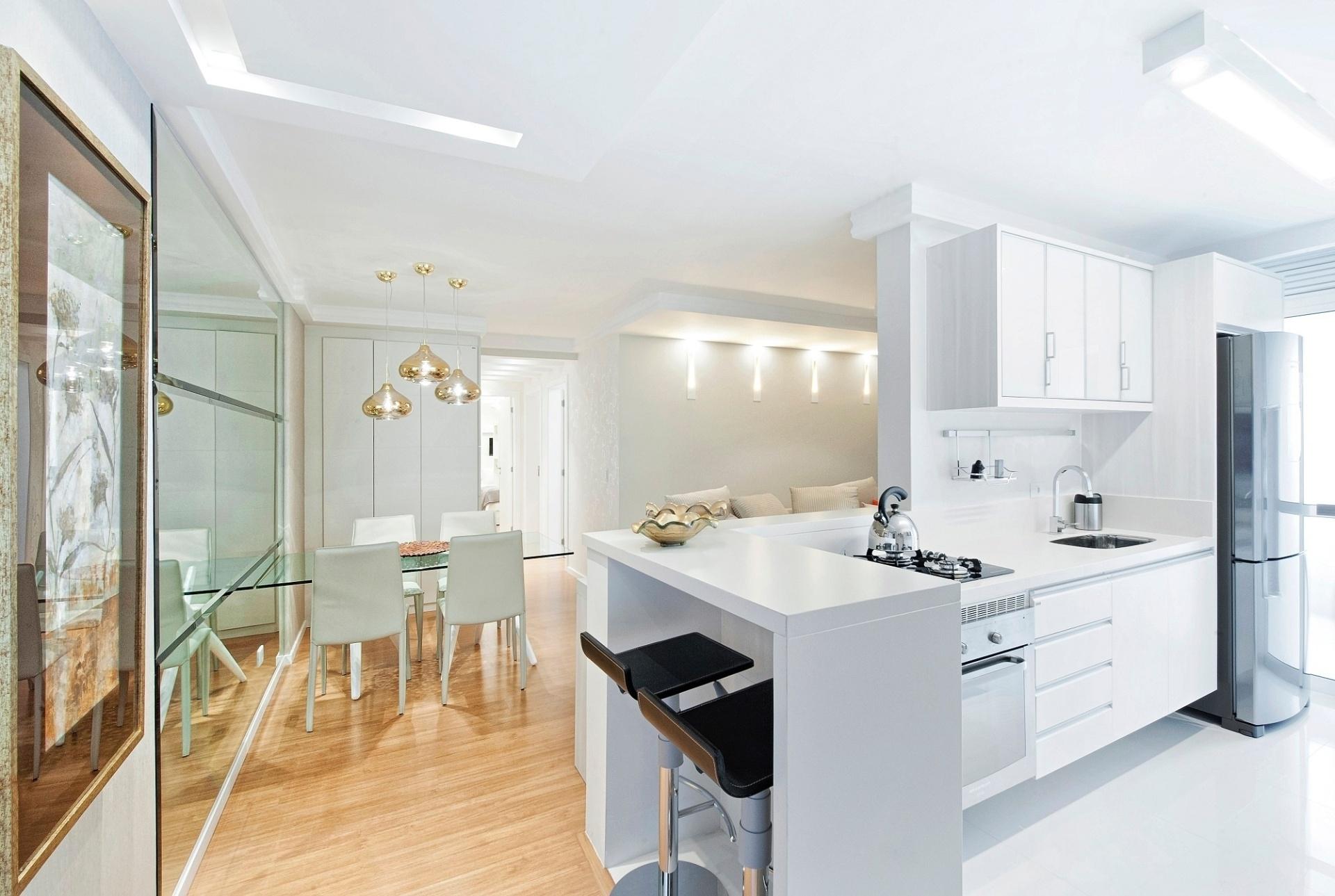 No apartamento em Curitiba (PR), o escritório Carla Kiss Arquitetura integrou a cozinha aos ambientes sociais para dar mais amplitude ao espaço. Para que a decoração não ficasse monótona, o projeto balanceou as cores claras com elementos dourados