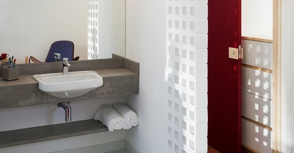 No apartamento reformado pelo Grupo Garoa Arquitetos, o lavatório do banheiro recebeu uma parede divisória composta por elementos vazados em concreto 10 x 10 cm, pintados de branco. A bancada também em concreto, porém sem acabamento, tem cuba embutida e a iluminação é feita por uma régua acima do espelho