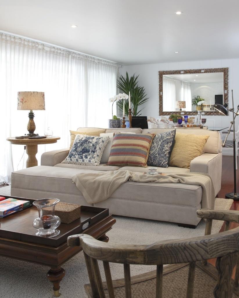 Nesta sala, o conforto também é enfatizado pela escolha dos materiais: o escritório In House Designers de Interiores propôs um estofado com pufe revestido de suede, que, nos dias frescos, fica mais quentinho com a gostosa manta. O tapete sobre o piso de madeira dá ainda mais conforto