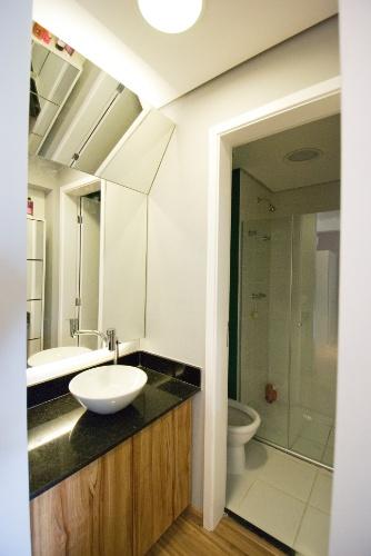 No banheiro do apartamento com 35 m², decorado pelo arquiteto Leandro Matsuda, a inclinação do espelho permite que os moradores se enxerguem de corpo inteiro