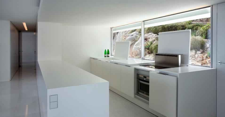 A cozinha voltada para a janela dos fundos tem estilo