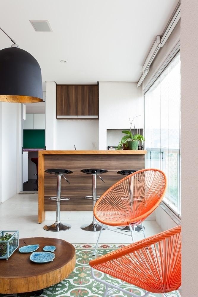 Assinada por Merê Esteves + Lucchesi Razuk Arquitetura, a varanda gourmet com 22 m² tem área para churrasqueira composta por um pequeno balcão e uma pia. No projeto, os profissionais mantiveram o piso de ladrilhos hidráulicos original do imóvel