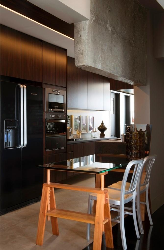 Integrada à sala, a cozinha do apartamento do arquiteto Maurício Karam tem um mix equilibrado de acabamentos: madeira escura nos armários, porcelanato no piso e concreto aparente nas paredes. Anexa a uma das bancadas, a mesa de jantar é definida por um tampo de vidro e conta com pés em formato cavalete