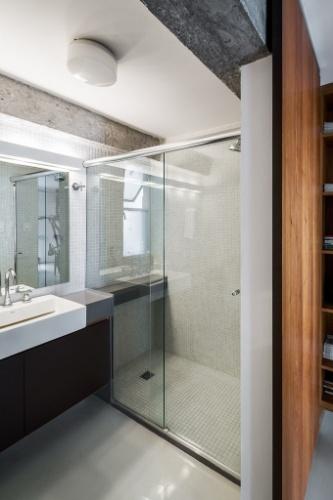 O banheiro recebeu revestimentos claros, que ajudam a dar maior sensação de amplitude: pastilhas decoram toda a área do boxe e a parede atrás do espelho, o único ponto escuro é o gabinete sob a pia. O projeto de reforma do apartamento no edifício Gemini foi realizado pelo arquiteto Takuji Nakashima, que também mora no local